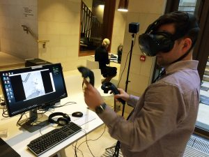Man with VR headset stands in front of computer monitor with VR controllers in hand.