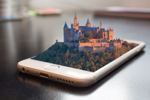A phone with a castle coming out of the screen in 3D effect
