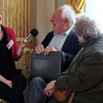 A woman interviews an elderly couple, they are all laughing