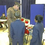 A man in WW1 soldier uniform talks to school children