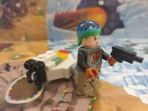 Sabine Wren stands in front of the Ghost, blaster pistol in her left hand, facing outwards.